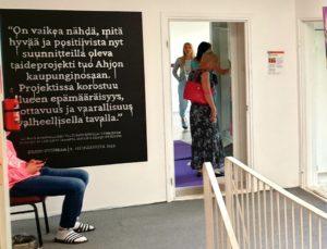 Rappukäytävä, jonka seinällä taulu ja oviaukossa ihmisiä.
