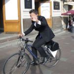 Juhlavasti pukeutunut mies pyöräili elokuussa Nevski Prospektin jalkakäytävällä.