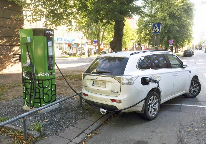 Sähköautojen latauspisteiden paikat vaihtelevat automalleittain ja siksi kadunvarsipysäköinti voi olla käyttäjän kannalta epäkäytännöllinen. Kuvan lataustoimenpiteestä on rapsahtanut sakko virhellisen pysäköinnin johdosta.