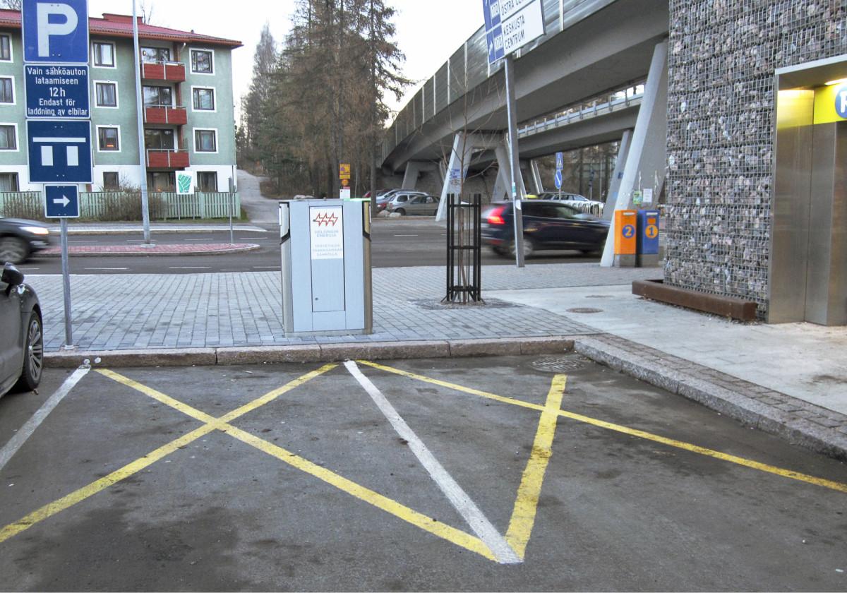 Peruslatauspiste kahdelle autolle Helsingin Siilitien metroasemalla. Helsingin kaupungilla on käynnissä kokeilu, jossa latauspisteen parkkiruutuun maalataan keltainen rasti.