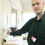 Toimitilapäällikkö Jarmo Airaksinen ja suoraa sähkölämmitystä ohjaava termostaatti. Sen alle kytkentärasiaan on asennettu radiotaajuudella ohjattava pienikokoinen rele, joka kytkee lämmön päälle tai pois. Termostaatti on siis luovuttanut lämpötilaan liittyvän, alueellisen määräysvaltansa järjestelmän keskusyksikölle.