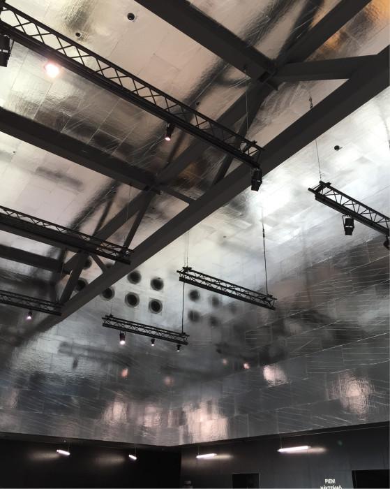 Yleisölämpiön seinien ja katon foliopinta heijastaa valoa ja värejä.