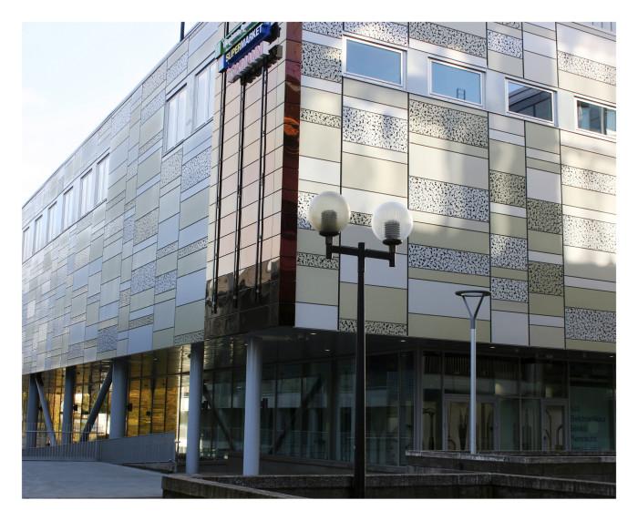 Laserkuvioidut teräslevyt peittävät kauppakeskuksen seinien ulkopintaa. Ylimmän kerroksen ikkunat kuuluvat teatterin tuotantotiloihin.