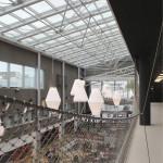 Yleisölämpiö aukeaa parvekemaisesti kauppakeskukseen. Teräsverkosta tehty taideteos toimii näkösuojana.