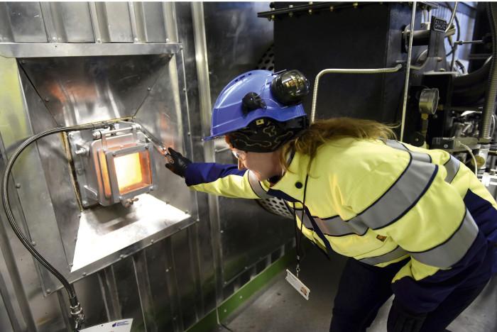 Tammervoima Oy:n turvallisuuskoordinaattori Tiina Elomaa kurkistaa arinalle lasiluukun läpi Tarastenjärven laitoksen koekäyttövaiheessa marraskuussa.