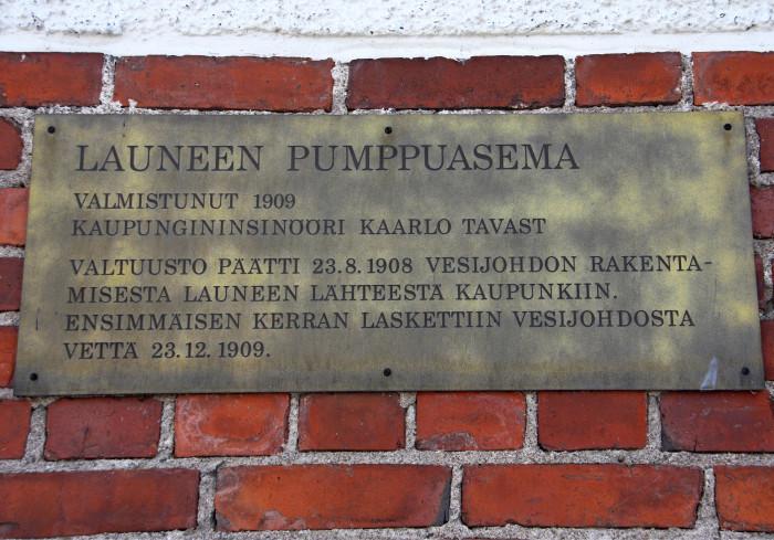 Kilpi pumppaamorakennuksen seinässä todistaa vedenottamon pitkää historiaa. Kuva: Paavo Taipale