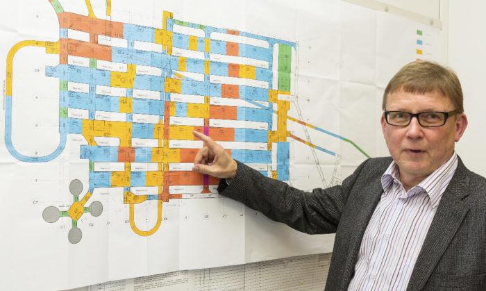 Investoinnit-osaston johtaja Tuomo Heinonen esittelee tunnelipuhdistamon piirustusta. Puhdistuslaitteisto sijoitetaan vaakasuunnassa oleviin tunneleihin. Neliapila vasemmassa alakulmassa esittää tulevan mädättämön neljää säiliötä.