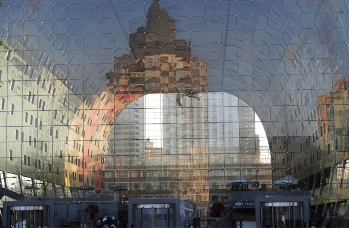 Kauppahallin sisäänkäynti heijastaa ja näyttää vastapäisiä ja naapurirakennuksia.