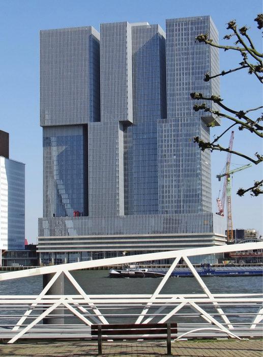 Rem Koolhaas (OMA) suunnitteli kolmen tornin kokonaisuutensa Kop van Zuidin alueelle jo 1998. De Rotterdam –niminen tornikompleksi toteutui vasta 2013 sen jälkeen kun kaupunki päätti vuokrata keskimmäisestä tornista tiloja muun muassa kaupunkisuunnitteluvirastolle. Tornien 40-metrin korkuiset jalustaosat sisältävät paitsi pysäköintiä niin myös tiloja vapaa-ajan toiminnoille. Läntisin torneista on asuinrakennus ja itäisessä tornissa sijaitsee toimistotilojen lisäksi hotelli.