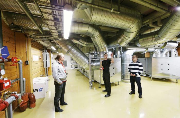 Halkaisijaltaan jopa 600 millimetrin ilman- vaihtoputket haarautuvat eri puolille koulua. Toisen kerroksen teknisessä tilassa ovat Lemminkäisen kiinteistöpäällikkö Ville Sormunen (vas.), ylläpidon työnjohtaja Harri Kujala ja rehtori Mikko Lumme.